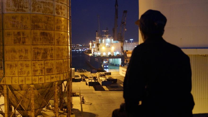 Un chico observa cómo introducen las mercancías en uno de los barcos con destino a la península.