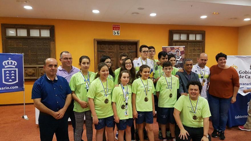 Miembros del equipo de ajedrez que ha participado en los 'XXXIV Campeonatos de Canarias en Edad Escolar' con el presidente de la Federación Canarias de Ajedrez, José Carlos Martín (i), y la consejera de Deportes del Cabildo de La Palma, Ascensión Rodríguez (d).