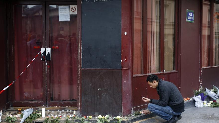 Un hombre enciende una vela en frente de Le Carillon, escenario de uno de los tiroteos. / AP Photo/Jerome Delay