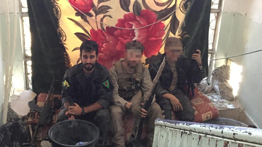El joven miliciano de las YPG (izquierda) junto a otros dos combatientes del grupo en la ciudad de Raqqa.
