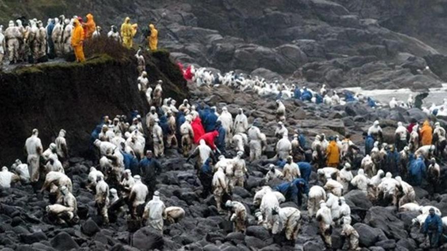 Voluntarios limpiando las playas gallegas tras el vertido del Prestige
