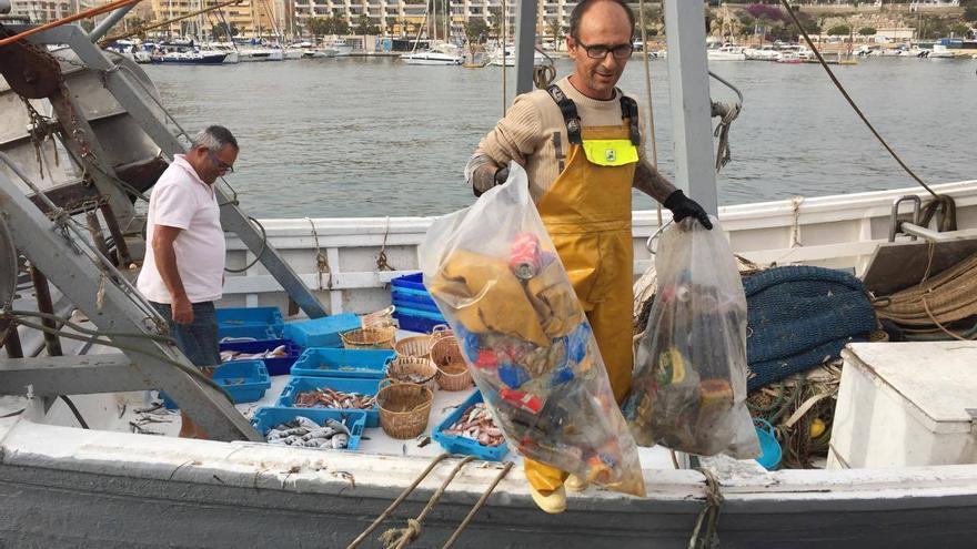 Un pescador saca dos bolsas de residuos