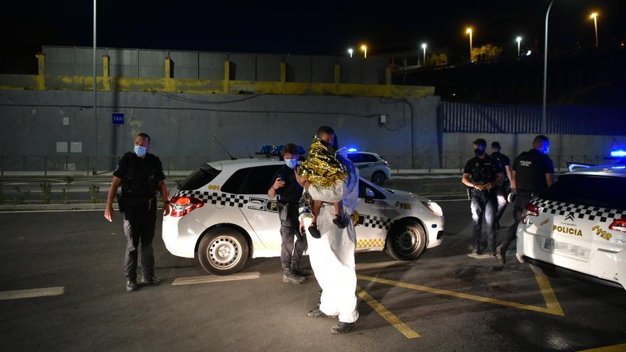 Un hombre migrante junto a policías en Ceuta tras acceder de forma irregular a la ciudad española