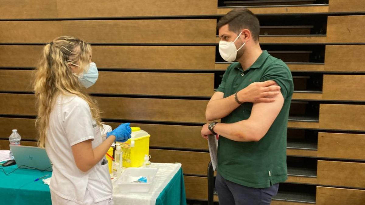 Una sanitaria dialoga con un joven después de ser vacunado contra el coronavirus en Gandia.