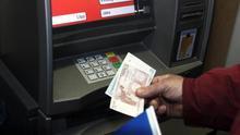 Un usuario saca dinero en un cajero automático.