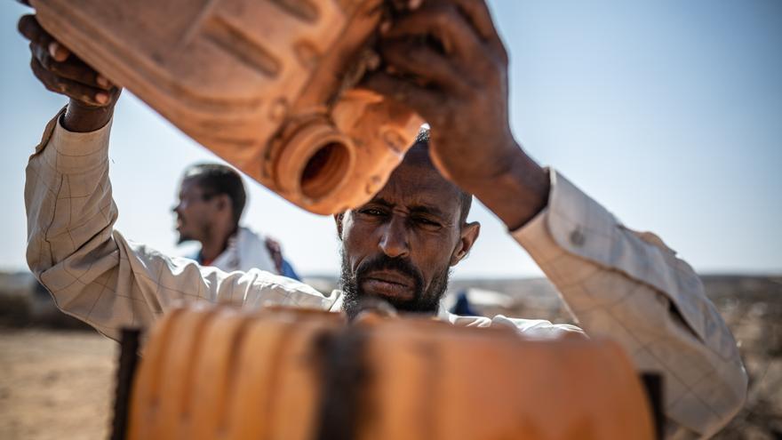 Alí recarga un bidón de agua colocado al lado de las letrinas utilizado para el lavado de manos. Foto: Pablo Tosco / Oxfam Intermón