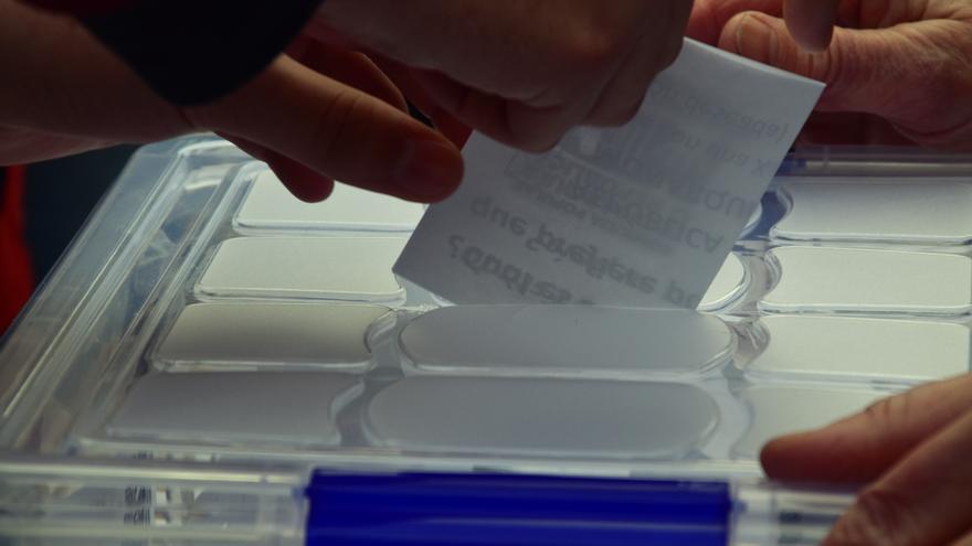 Una persona introduce su voto en una urna en la consulta popular Monarquía o República 2D celebrada en Madrid.