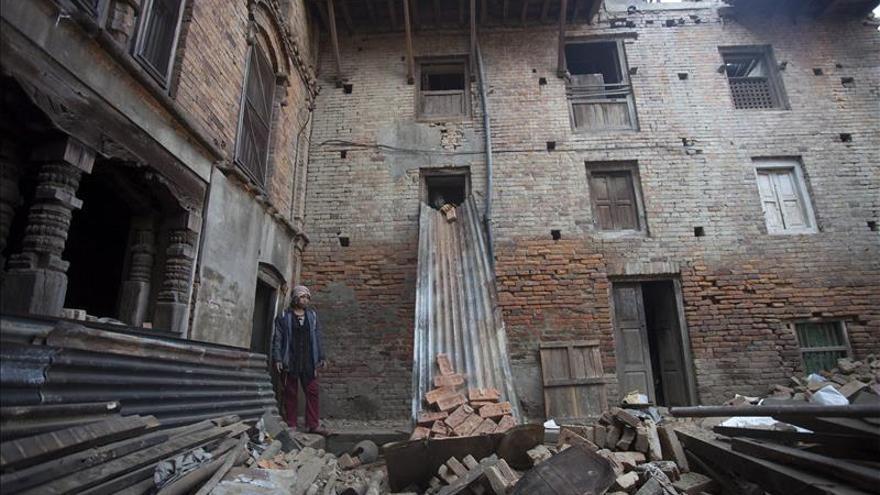 Varias personas recogen ladrillos reutilizables de un edificio en ruinas durante los trabajos de reconstrucción en Bhaktapur (Nepal). / Efe.