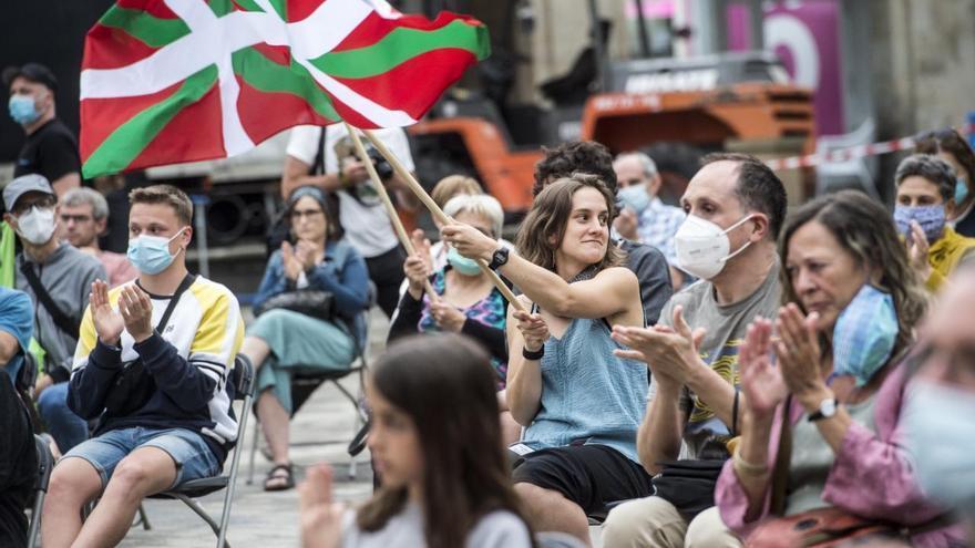 Una joven ondea una ikurriña en el mitin de apertura de campaña de EH Bildu en la Plaza de España de Vitoria