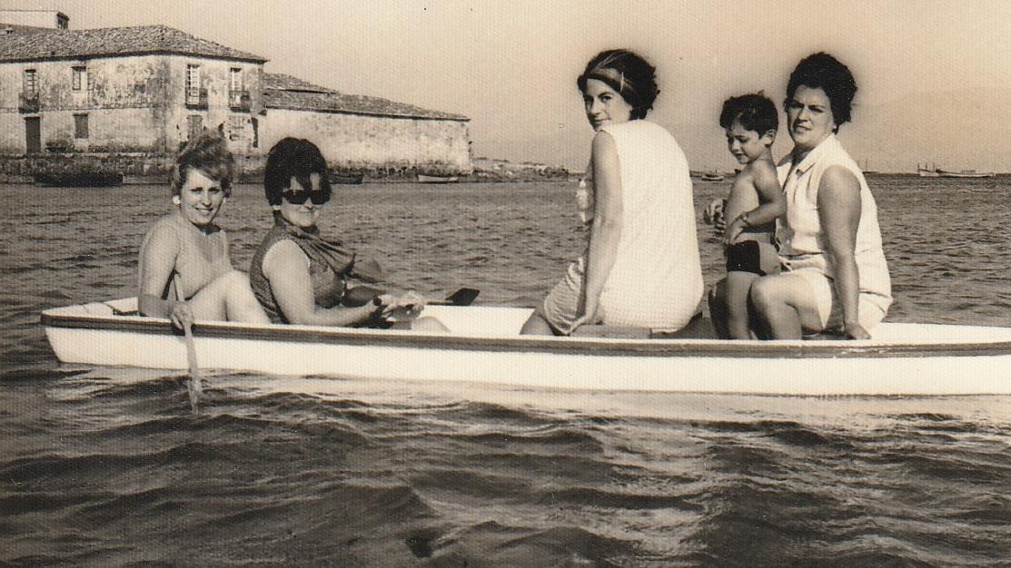 Una mujer y sus cuñadas, alrededor de 1965, en un barquito delante de la playa de Rocha, frente a los edificios de fábricas conserveras, en Muros