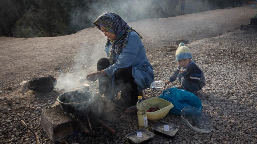 Una madre con su hijo calientan en un hornillo la comida oficial del Ejército
