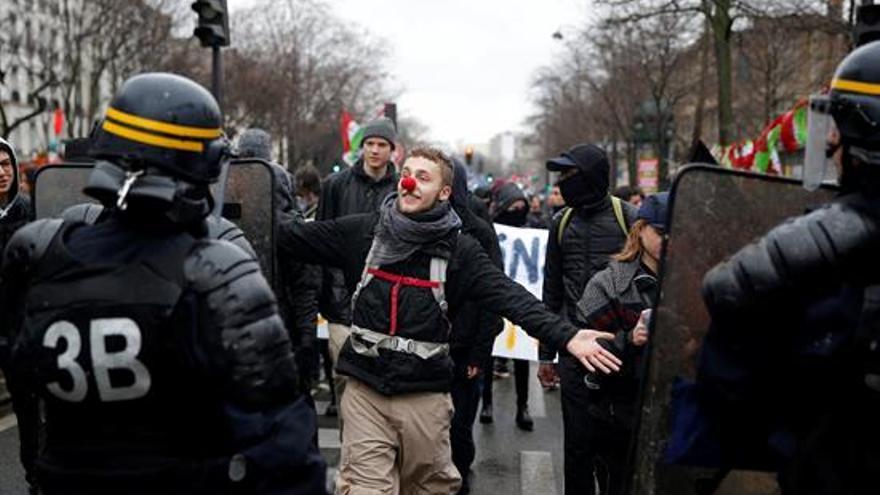 Un manifestante se coloca una nariz de payaso ante varios agentes de policía durante una protesta este jueves en París (Francia)