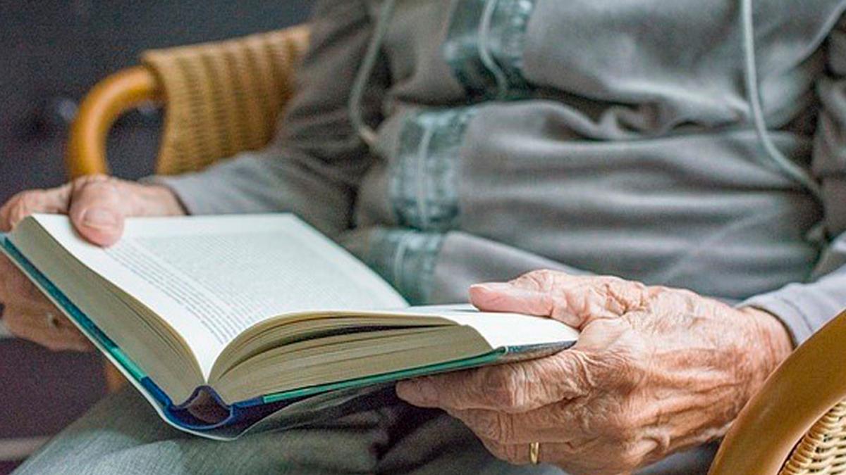 Una anciana dependiente lee un libro.