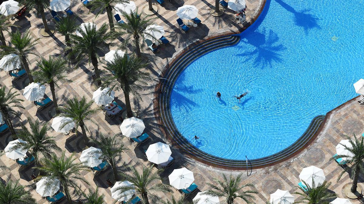 Gente nadando en la piscina de un hotel