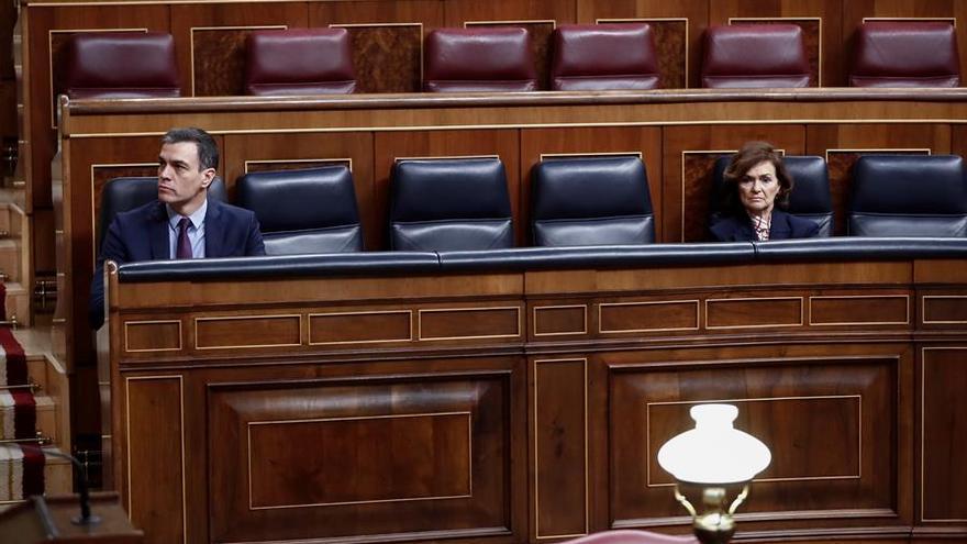 El presidente del Gobierno, Pedro Sánchez, con la vicepresidenta primera del Ejecutivo, Carmen Calvo, a su izquierda, en su escaño del hemiciclo del Congreso momentos antes de explicar la declaración del estado de alarma