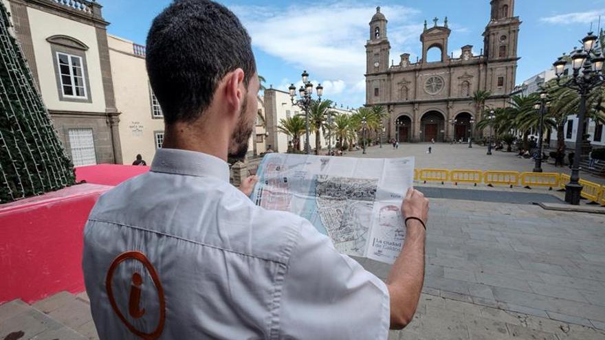 """Un guía turístico de Las Palmas de Gran Canaria sujeta el folleto """"La ciudad de Galdos"""", un recorrido auto-guiado por los principales puntos de la ciudad relacionados con la de Galdós"""