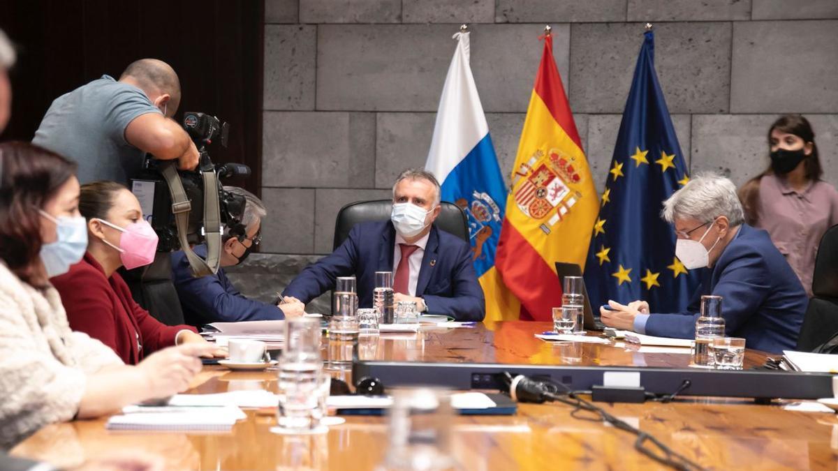 El presidente del Gobierno de Canarias, Ángel Victor Torres (c), junto al portavoz del Ejecutivo, Julio Pérez (d) durante la reunión del Consejo de Gobierno que se ha celebrada este jueves