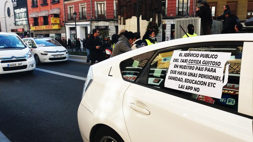 """Un taxi en la calle Atocha con un cartel: """"El servicio público del taxi cotiza gustoso""""."""