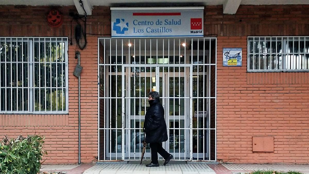 Una mujer pasa delante de la puerta del edificio antiguo del centro de salud Los Castillos.
