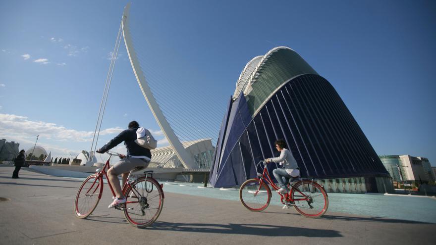Dos ciclistas pasan por delante del Ágora de la Ciudad de las Artes y las Ciencias de Valencia