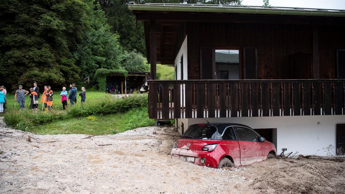 Un coche aparece semienterrado por las inundaciones en Schoenau am Koenigssee, Alemania.