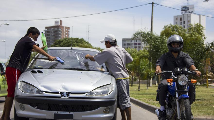 Dos 'pibes vidrio' limpian el parabrisas de un coche en la ciudad argentina de Santa Fe.