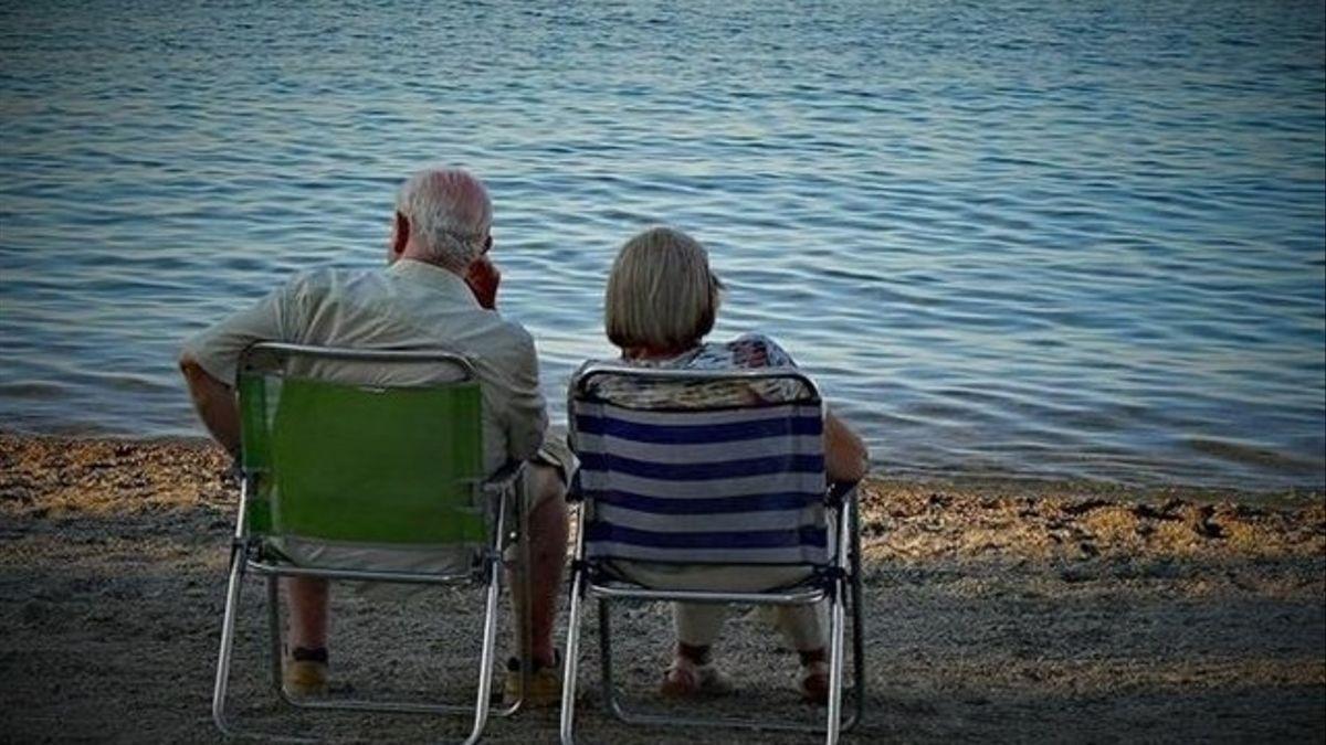 Dos personas mayores en la playa en una foto de archivo.