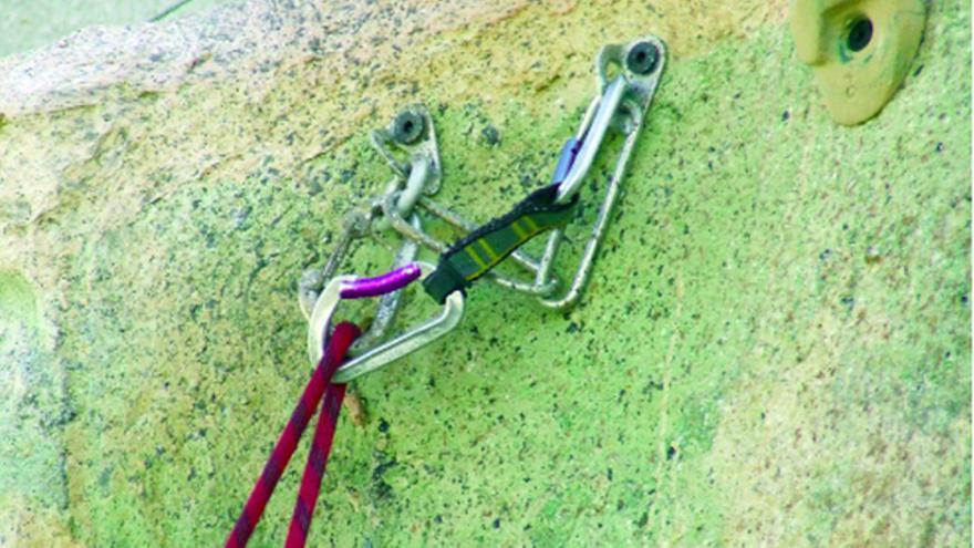 Descuelgue mal realizado para la escalada en polea en rocódromo. Dos mosquetones alineados en cierres sin ser de seguridad.
