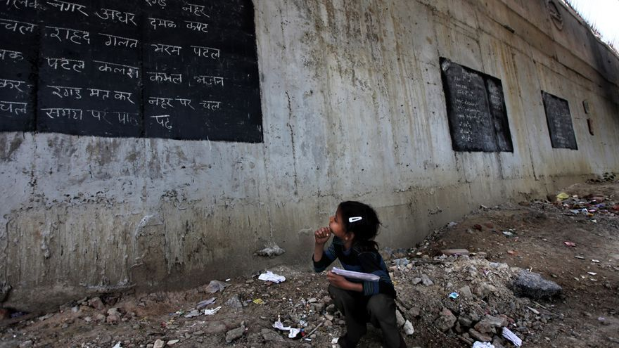 Una niña toma apuntes de una pizarra pintada en una pared del edificio de una escuela instalada bajo un puente de tránsito masivo en Nueva Delhi, India./ Fotografía: Altaf Qadri (AP)