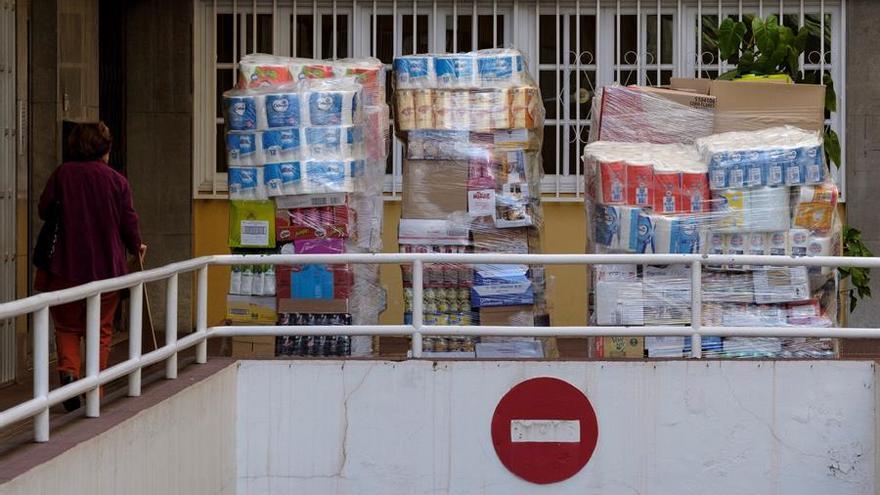 Una mujer pasa junto a unos palet de mercancías listos para reabastecer un pequeño supermecado de Las Palmas de Gran Canaria. EFE/Ángel Medina G.