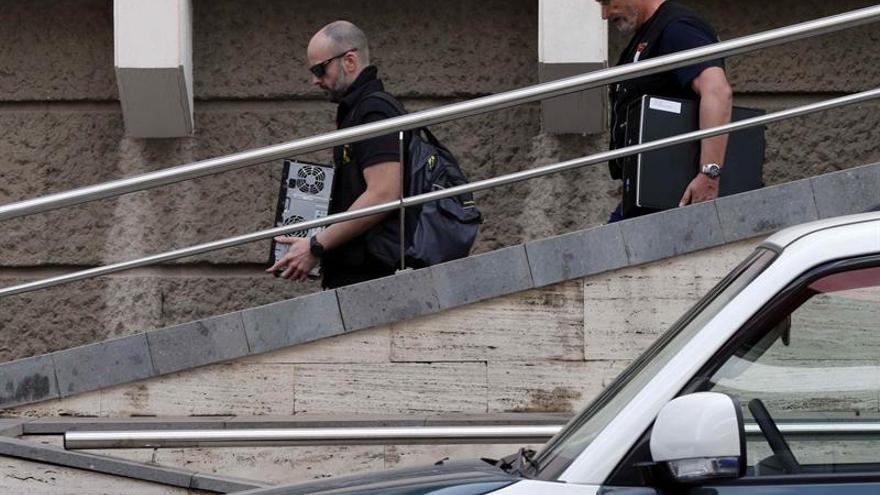Dos agentes de la Policía Judicial de la Guardia Civil se llevan dos discos duros de la oficina del catastro. EFE/Elvira Urquijo A.