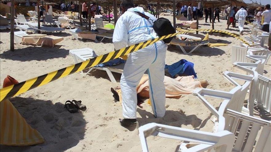 Un policía examina a dos víctimas del ataque terrorista en uno de los hoteles de Susa. / Efe