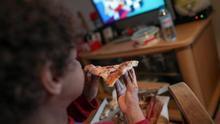 Un niño come un trozo de pizza del menú infantil de Telepizza mientras ve la televisión en su casa