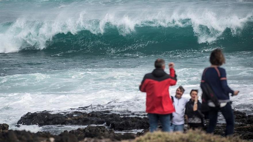Varias personas observan esta tarde el fuerte oleaje en la zona de Jameos del Agua, al norte de Lanzarote