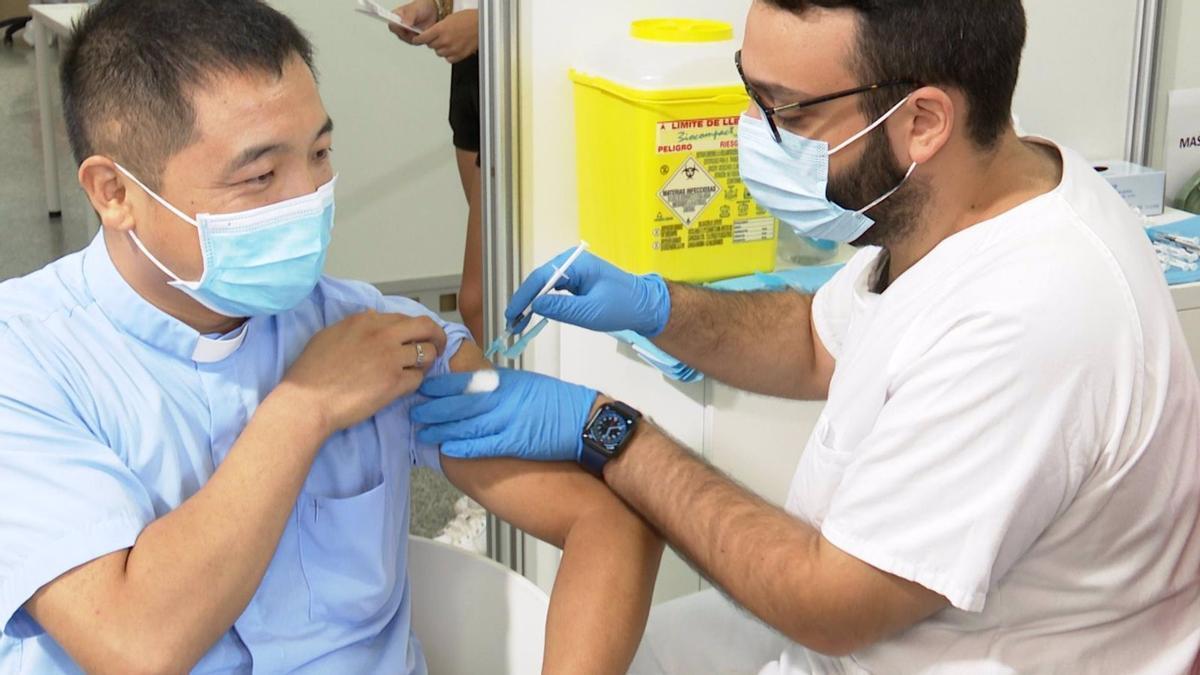 Un sanitario vacuna a un hombre en València en la primera jornada de vacunación sin cita previa.