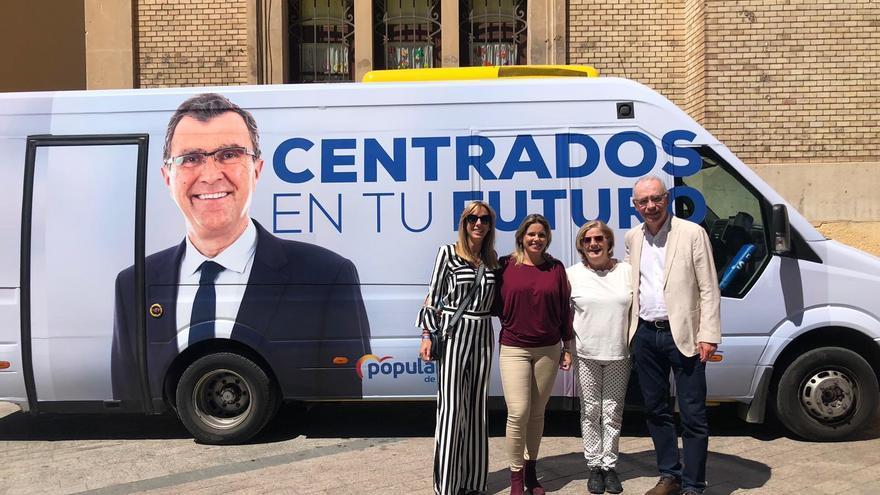 Simpatizantes del PP posan con el autobús que promociona la campaña de José Ballesta a la alcaldía de Murcia