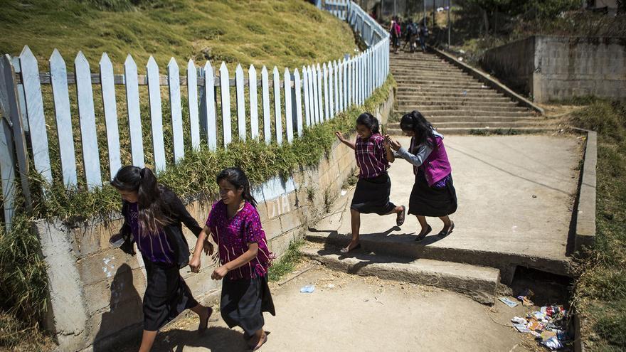 Asustadas por la presencia de una cámara, unas niñas corren tras salir de la escuela en San Juan Atitán