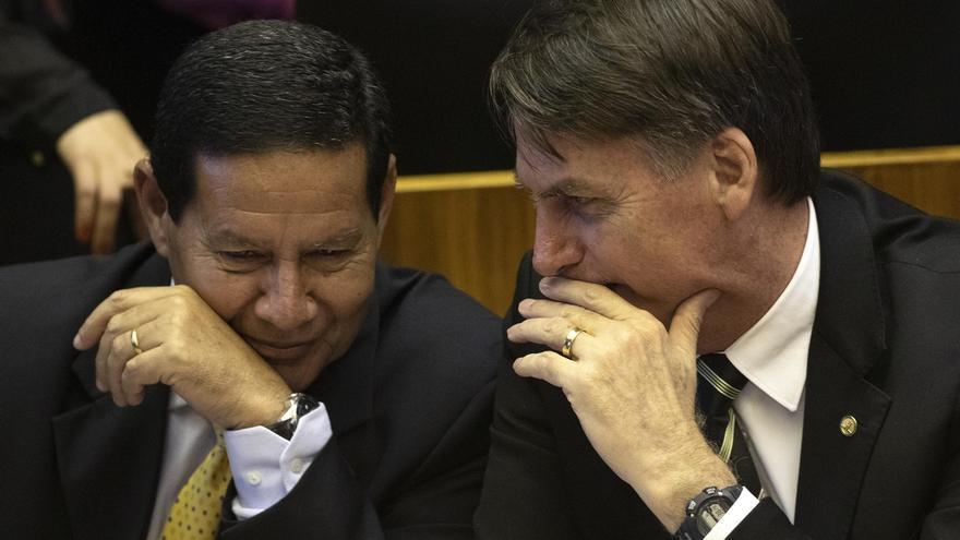 En la imagen un registró del presidente de Brasil, Jair Bolsonaro (d), al conversar con su vicepresidente, Hamilton Mourao (i), en Brasilia (Brasil).