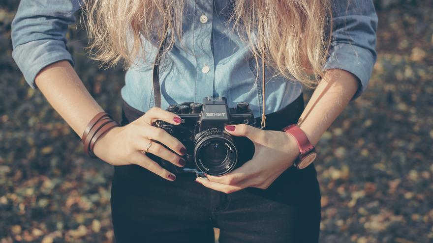 Una joven con su cámara de fotos en la naturaleza. / Foto: Sergei Zolkin
