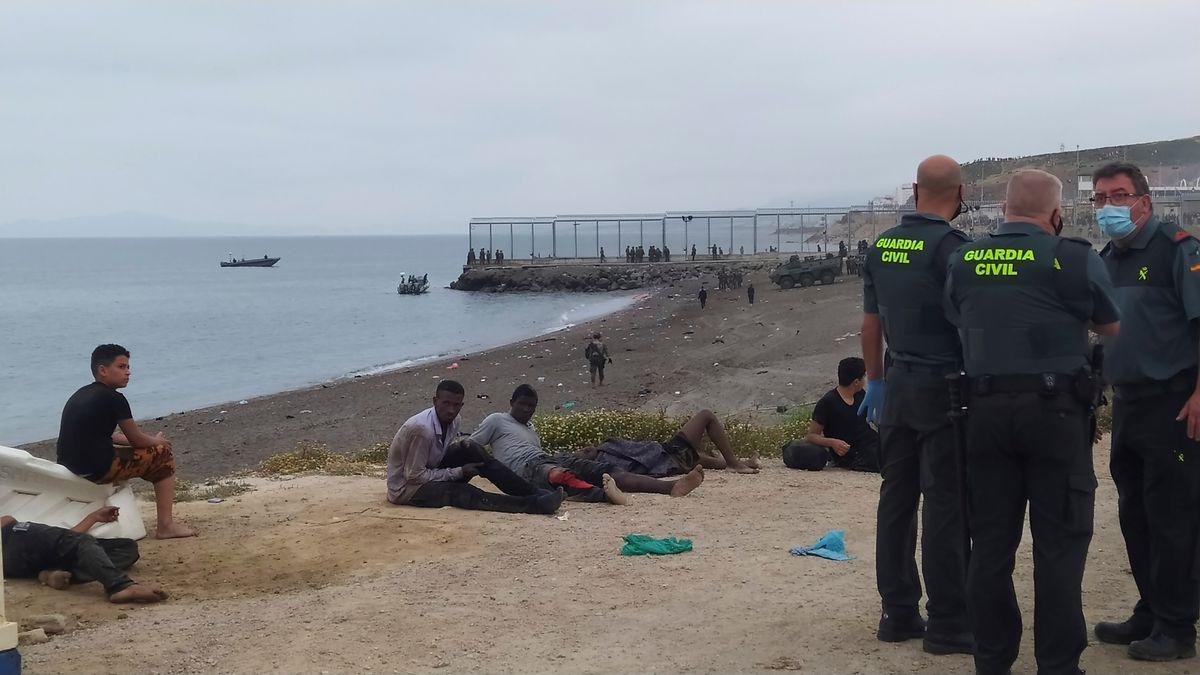 Miembros de la Guardia Civil conversan junto a un grupo de migrantes que han cruzado la frontera a nado por los espigones fronterizos de Ceuta, donde este se batió la cifra récord de llegada de migrantes a España en un solo día por vía marítima