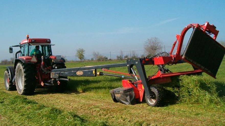 Un tractor trabaja con maquinaria agrícola en el campo.