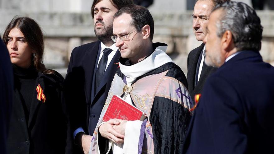 El prior de la Basílica Santiago Cantera junto a los familiares de Francisco Franco tras introducir el féretro con los restos mortales del dictador en el coche fúnebre.