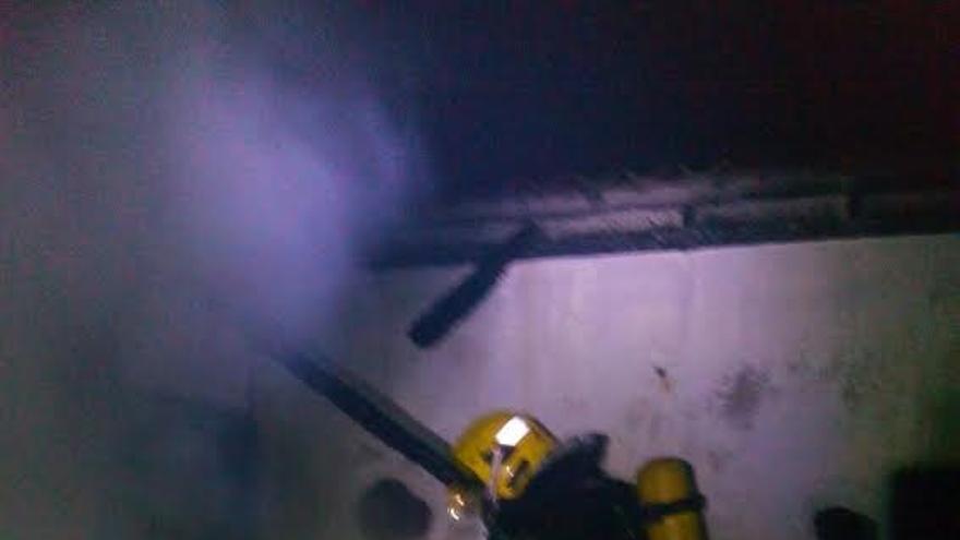 En la imagen, uno  de los bomberos durante la tarea de extinción del incendio en una casa de Garafía. Foto: BOMBEROS LA PALMA.