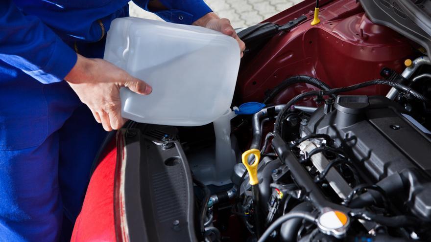 Un mecánico rellena el filtro del agua de un vehículo.