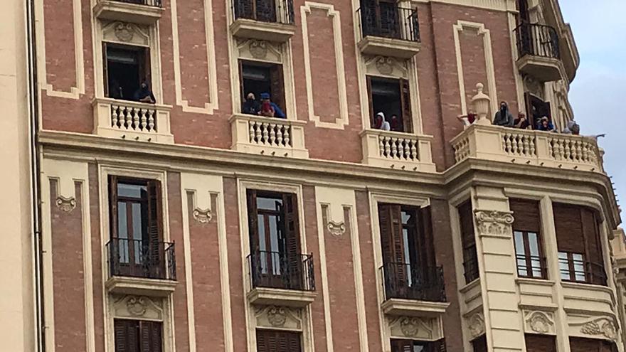 Encapuchados en un edificio por el que pasan las manifestaciones