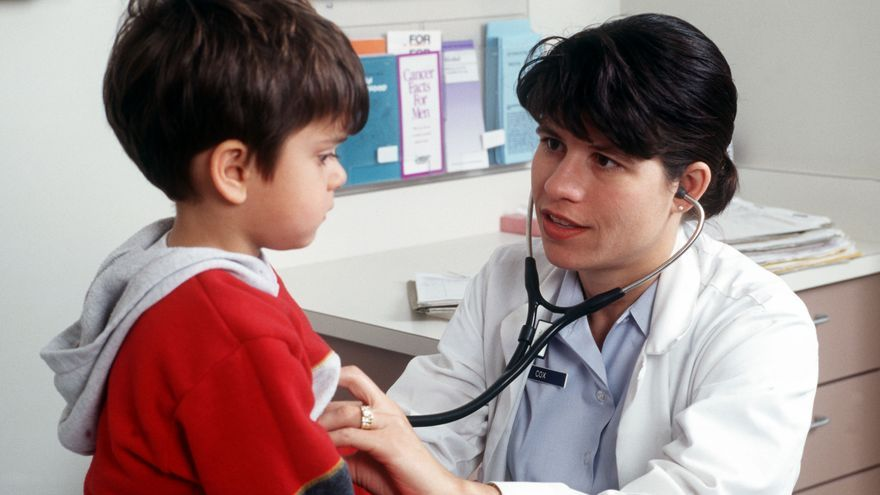 Una doctora explora a un niño durante una consulta.