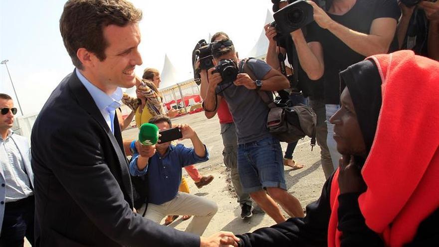 Pablo Casado saluda a un grupo de migrantes durante su visita a Algeciras (Cádiz).