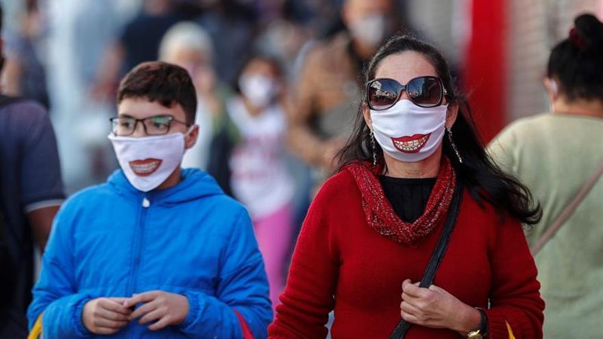 Personas con tapabocas caminan frente a tiendas cerradas por la situación del coronavirus el 29 de mayo de 2020 en la ciudad de Sao Paulo (Brasil).