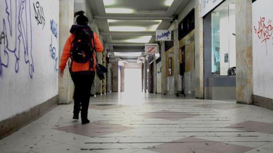 Una mujer camina por una galería comercial vacía