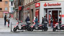 Varias personas esperan para entrar a una oficina del Banco Santander